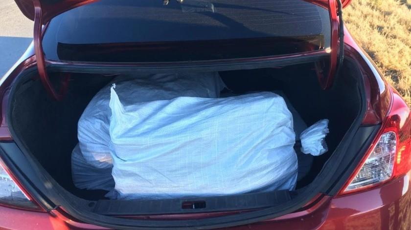 Personal de la Guardia Nacional solicitó al conductor una revisión de rutina, asegurando de los asientos posteriores y cajuela 10 costales de ixtle con 10 recipientes de plástico cada uno.(Especial)