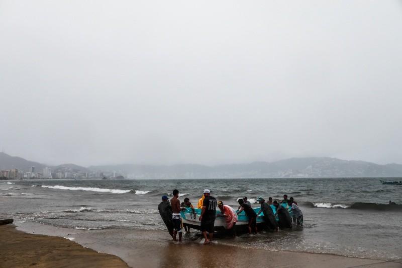 Varias personas retiran un bote de las aguas por el paso de la depresión tropical Dolores en el balneario de Acapulco (México). EFE/ David Guzmán